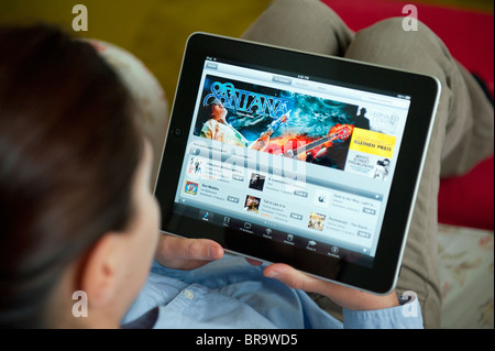 Woman using iPad tablet computer at home to browse iTunes digital music store - Stock Photo