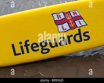 Lifeguards' surfboard on sand - Stock Photo