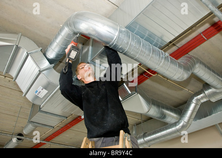Ventilation fitter installing a ventilation pipe - Stock Photo