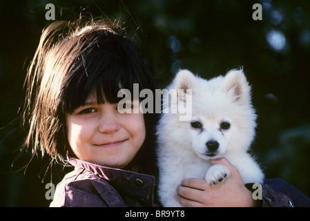 1990s EIGHT-YEAR-OLD GIRL HOLDING WHITE PUPPY AMERICAN ESKIMO SPITZ - Stock Photo