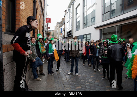 Dublin, Ireland; A Crowd Gathers In The Street To See A Performer For Saint Patrick's Day - Stock Photo
