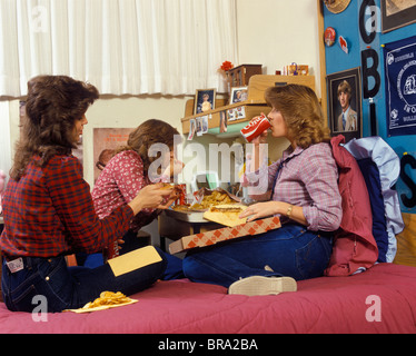 1980s THREE TEENAGE GIRLS EATING PIZZA AND FRENCH FRIES AND DRINKING CANNED SODA IN DORM ROOM - Stock Photo
