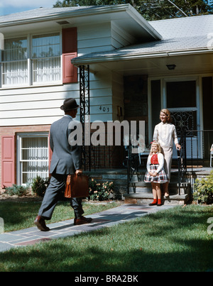 1950s MOTHER DAUGHTER WAITING STEP SUBURBAN HOUSE FATHER BRIEFCASE COMING HOME MAN WOMAN GIRL FAMILY RETRO - Stock Photo