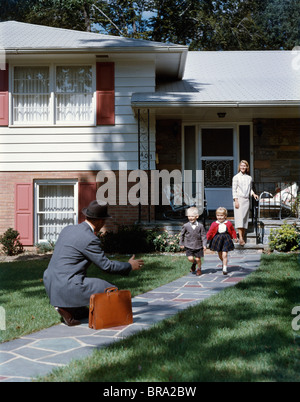 1950s FATHER MAN COMING HOME KNEELING ARMS EXTENDED BOY GIRL RUNNING WELCOME HOME WOMAN WIFE SUBURAN HOUSE FAMILY - Stock Photo