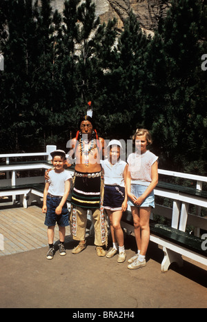 1950s BOY AND TWO LITTLE GIRLS POSING WITH AN NATIVE AMERICAN INDIAN IN SOUTH DAKOTA 1956 - Stock Photo