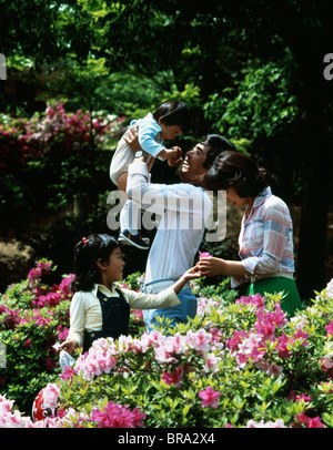1980s ASIAN FAMILY OF FOUR IN WOODS PICKING FLOWERS FATHER LIFTING UP CHILD - Stock Photo