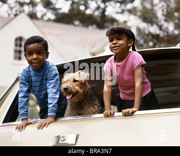1970s LITTLE AFRICAN-AMERICAN BOY AND GIRL LEANING OUT OF CAR WINDOW WITH DOG AIREDALE TRIP VACATION HAPPY - Stock Photo