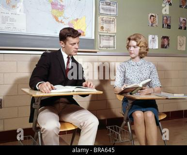 1960s TEENAGE BOY GIRL SEATED CLASSROOM DESKS TALKING STUDYING RETRO STUDENTS HIGH SCHOOL - Stock Photo