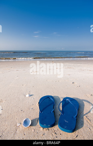 Pair of blue sandals on the sand at Holly Beach near Cameron, Louisiana on the Gulf Of Mexico. - Stock Photo
