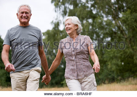 A senior couple walking through a field, holding hands - Stock Photo