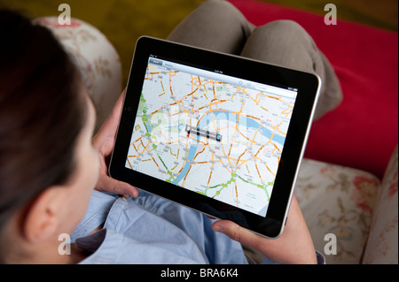 Woman using Google Maps application on iPad tablet computer to look at map of London - Stock Photo