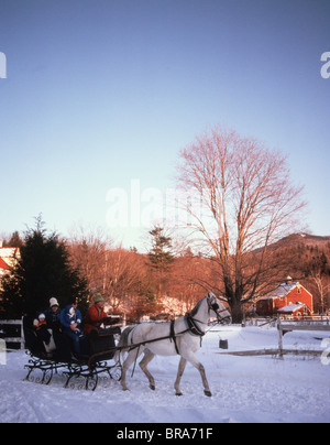 1980 1980s RETRO FAMILY RIDING THROUGH SNOW IN HORSE DRAWN SLEIGH - Stock Photo