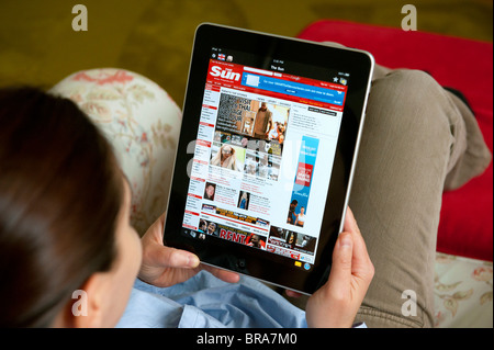 Woman using iPad tablet computer at home to read The Sun tabloid UK newspaper - Stock Photo