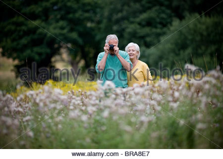 A senior couple taking photographs in a field - Stock Photo