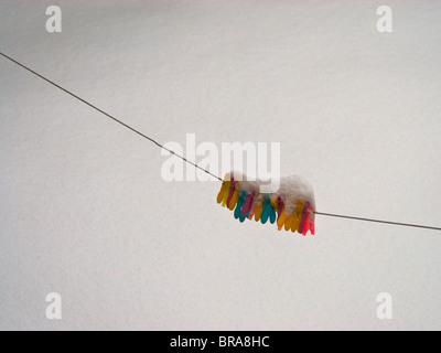 Colourful clothes pegs on a washing line in the snow. - Stock Photo