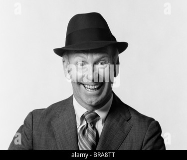 1960s MAN SMILING WEARING SUIT AND HAT WITH SILLY EAGER FACIAL EXPRESSION - Stock Photo