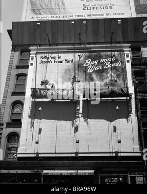 1940s 1945 NEW YORK CITY SIGN PAINTERS CORNER 42nd STREET FIFTH AVENUE PAINTING NEW WAR BONDS SIGN FROM SCAFFOLD - Stock Photo