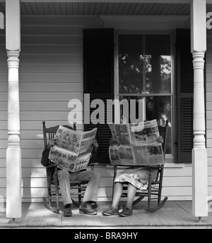 1950s 1960s COUPLE MAN WOMAN SITTING ON PORCH IN ROCKING CHAIRS HOLDING NEWSPAPERS UP HIDING THEIR FACES - Stock Photo