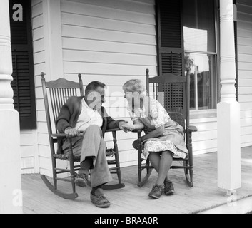 1970s ELDERLY COUPLE IN ROCKING CHAIRS ON PORCH HOLDING HANDS - Stock Photo