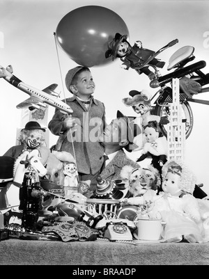 1950s FATHER WITH SON HOLDING BALLOON SURROUNDED BY TOYS & STUFFED ANIMALS - Stock Photo