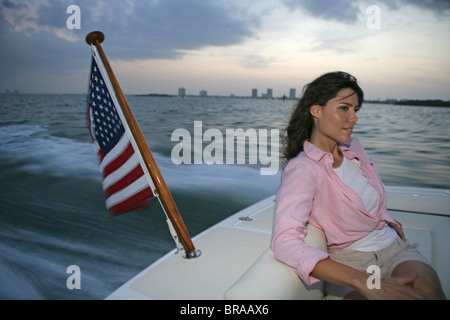 Woman sitting in the stern of a Hunt Harrier 25 off Hollywood, Florida, USA. Model and property released. - Stock Photo