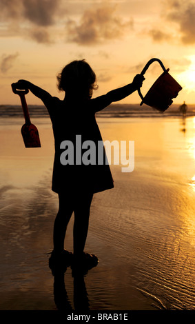 Little girl with bucket and spade silhouetted against setting sun on Summerleaze beach, Bude, UK. - Stock Photo