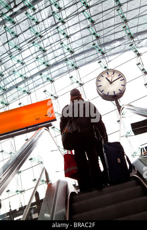Passenger on escalator and platform clock at modern train station, Berlin, Germany, europe - Stock Photo