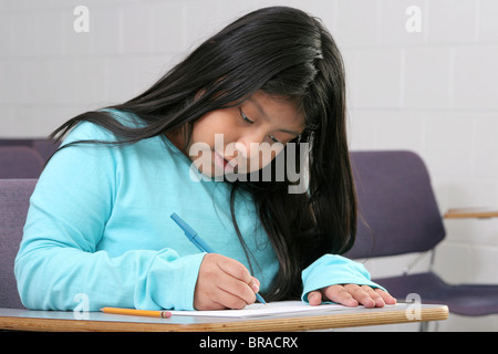 one young girl student writing in a classroom - Stock Photo