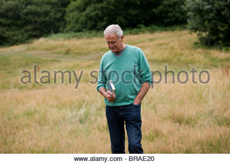A senior man standing in a field, holding a book - Stock Photo