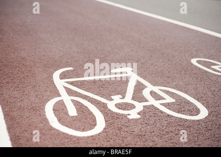 Designated Cycle Lane Symbol, Painted on a Red Asphalt Road Surface,  Brighton,  Sussex, England - Stock Photo
