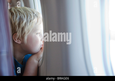 Young boy staring out plane window - Stock Photo