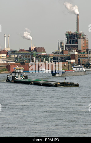 Boat traffic on the Rhine with Chempark Krefeld in background, NRW, Germany. - Stock Photo