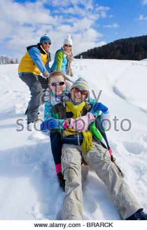 Parents on ski slope pulling children up hill on sled - Stock Photo