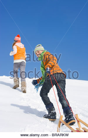 Brother and sister pulling sled up hill on ski slope - Stock Photo