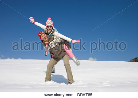 Father giving daughter piggyback ride while standing in snow - Stock Photo