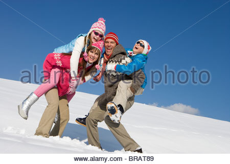 Parents giving children piggyback ride while standing in snow - Stock Photo
