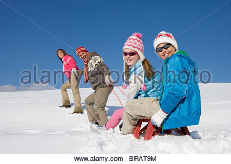 Father and mother pulling children uphill on sled - Stock Photo