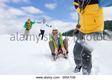 Man pulling wife through snow on sled - Stock Photo