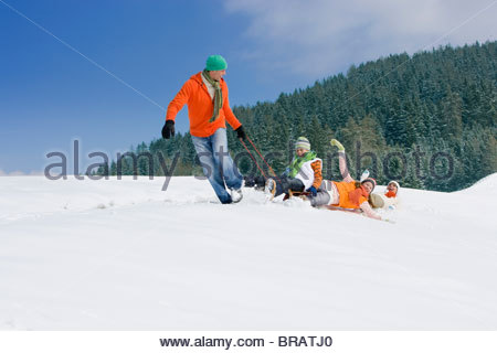 Father pulling family through snow on sled - Stock Photo