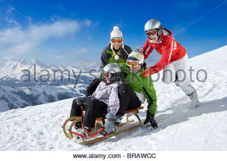 Family pushing sled downhill in snow on mountain top - Stock Photo