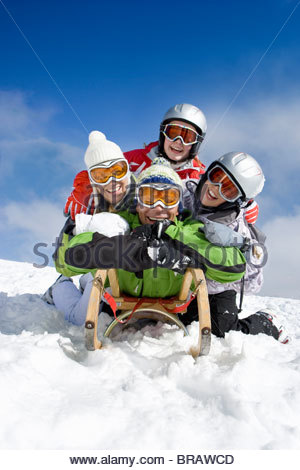 Family laying on sled in snow on mountain top - Stock Photo