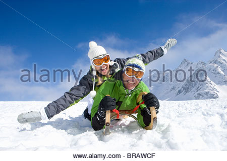 Couple laying on sled in snow on mountain top - Stock Photo