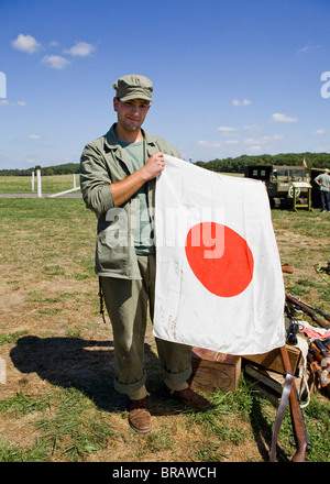 WWII era US army soldier holding Japanese flag - Stock Photo