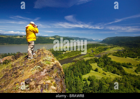 Hiker Taking Pictures At A Viewpoint In Columbia River Gorge National Scenic Area; Oregon, United States Of America - Stock Photo