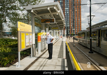 Man reading a sign at the Metrolink tram station at MediaCityUK, Salford Quays, Manchester, England, UK - Stock Photo
