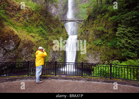 A Hiker Taking Pictures Of Multnomah Falls In Columbia River Gorge National Scenic Area; Oregon, United States Of - Stock Photo