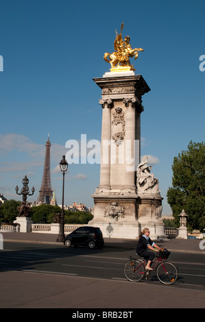 Woman cycling over Pont Alexandre III, Bridge of Alexander the Third, with Eiffel Tower in the background, Paris, - Stock Photo