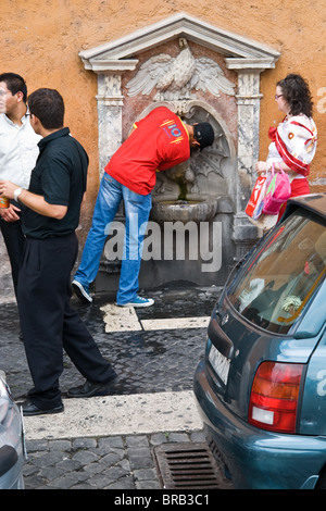 Drinking out of the water fountain near the Vatican Rome Italy - Stock Photo