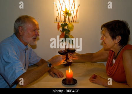 Elderly couple with a glass of wine by candlelight - Stock Photo