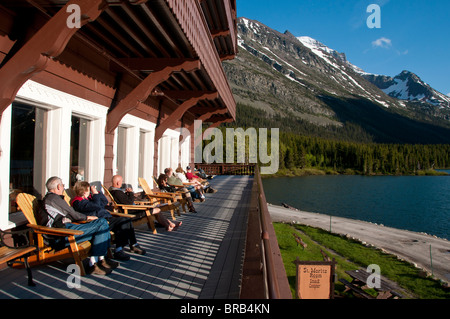 Folks relax and catch rays on the deck, Many Glaciers Hotel, Glacier National Park, Montana. - Stock Photo